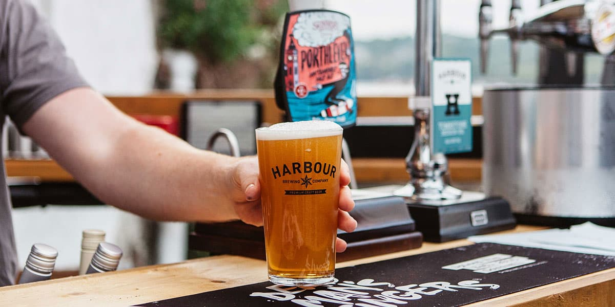A barman handing over a pint of Harbour Ellensberg at The Working Boat pub in Falmouth, Cornwall
